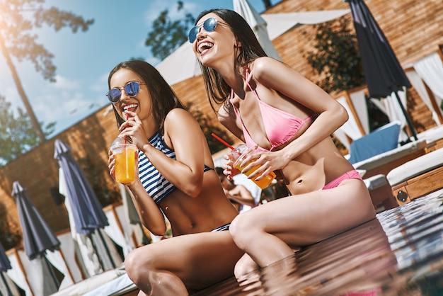 Godendo di due belle e felici giovani donne arancioni fresche in costume da bagno che sorridono e bevono freddo