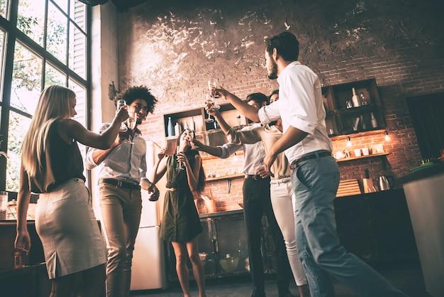 Godendo la festa con gli amici. inquadratura dal basso di giovani allegri che ballano e bevono mentre si godono la festa a casa in cucina