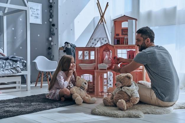 Godendo il tempo di gioco. padre e figlia giocano insieme con una casa delle bambole mentre