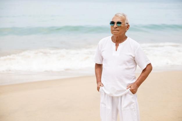 Godersi la pensione. uomo anziano felice che cammina sulla spiaggia.