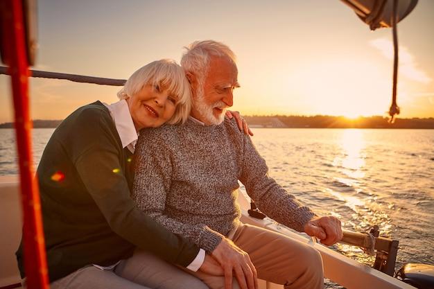 Godersi la vela al tramonto felice coppia anziana uomo e donna anziani che si tengono per mano abbracciando e