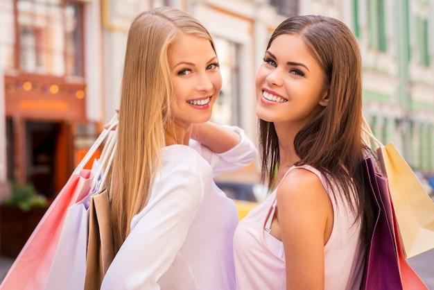Godersi lo shopping insieme. vista posteriore di due belle giovani donne che tengono le borse della spesa e si guardano alle spalle con un sorriso mentre stanno in piedi all'aperto