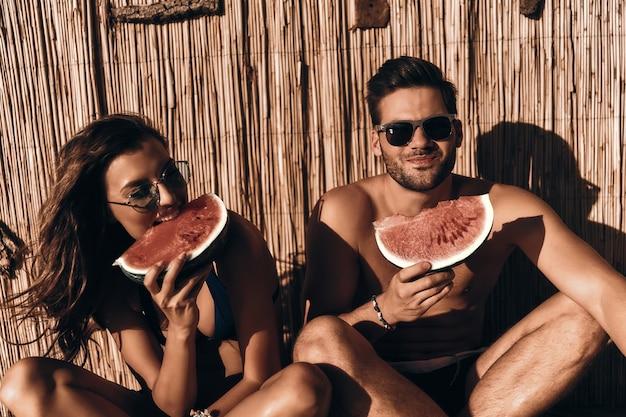 Godersi i rinfreschi estivi. bella giovane coppia che mangia anguria e sorride mentre è seduta all'aperto