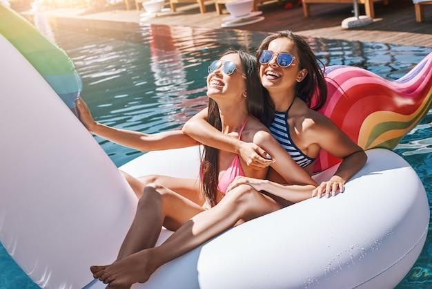Godendo l'estate due giovani donne giocose in costume da bagno che si divertono mentre galleggiano su un grande