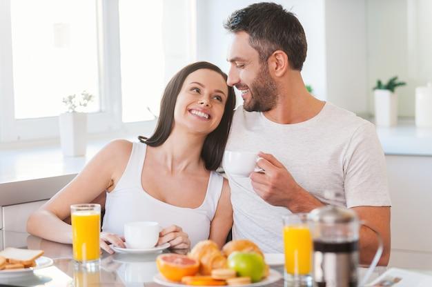 Godendo la domenica mattina insieme. bella giovane coppia che si lega e sorride mentre è seduta in cucina insieme e fa colazione