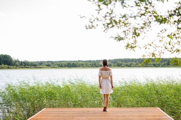 Godendo l'abbronzatura e le vacanze, la giovane bella donna resta sul molo della spiaggia di legno