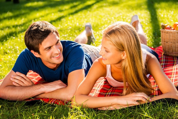 Godendo il loro appuntamento perfetto insieme. felice giovane coppia di innamorati che si rilassano nel parco insieme mentre sono sdraiati su una coperta da picnic e si guardano l'un l'altro