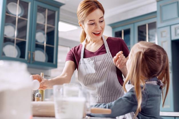 Divertirsi. gioiosa giovane donna si diverte con la sua piccola figlia mentre fa la pasta insieme e chiacchiera allegramente
