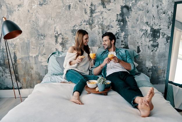 Godendo del tempo insieme. bella giovane coppia che fa colazione mentre trascorre il tempo a letto a casa