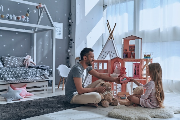 Godendo del tempo insieme. padre e figlia giocano insieme con una casa delle bambole mentre