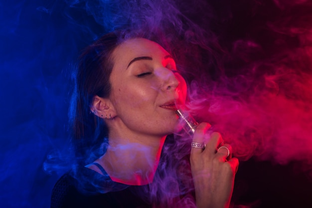 Godendo di donna con vape o sigaretta elettronica in fumo e luce al neon.