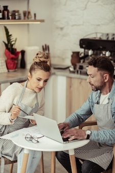 Ingrandire le idee. coppia sposata focalizzata che discute gli aspetti dello sviluppo per il loro caffè di famiglia.