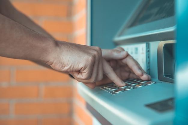 Inserire un codice della carta di credito sulla tastiera del bancomat