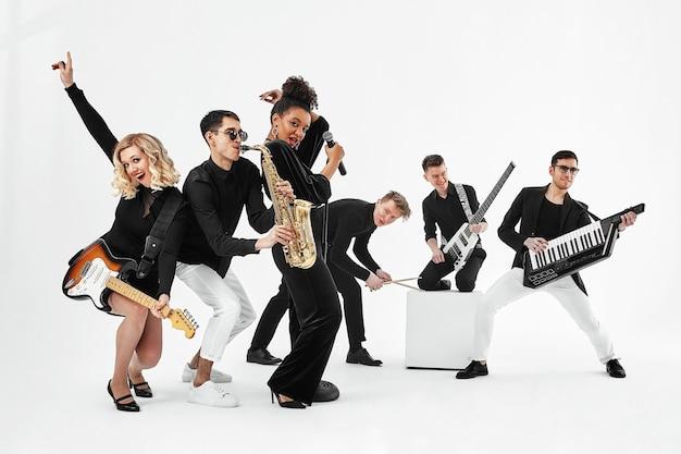 Concetto divertente, lavoro di squadra. gruppo internazionale di musicisti su sfondo bianco, chitarrista, batterista, solisti, sassofonista.