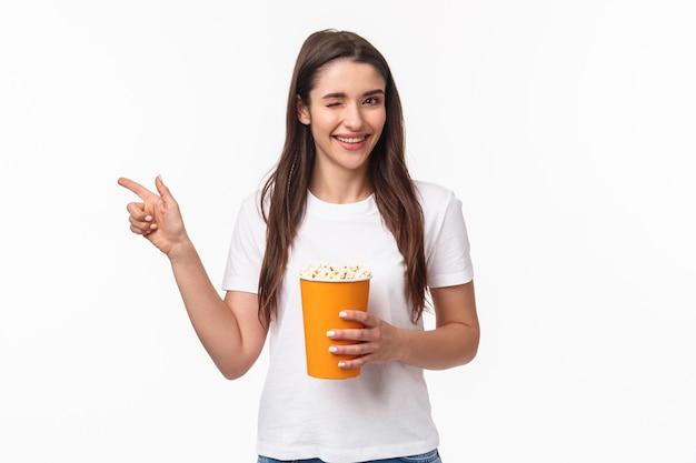 Concetto di intrattenimento, divertimento e vacanze. ritratto di sfacciato ragazza giovane carina in t-shirt, occhiolino e sorridente
