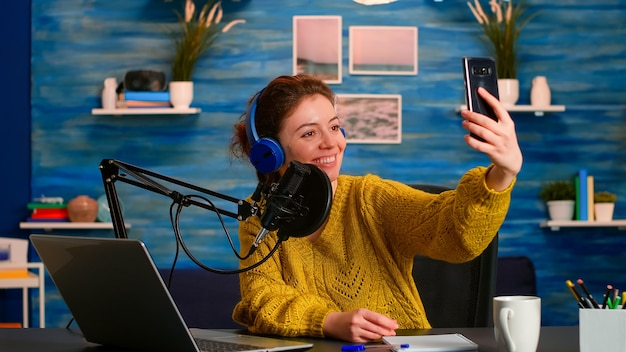 Podcast di intrattenimento che si fa selfie durante la trasmissione che lavora da casa studio