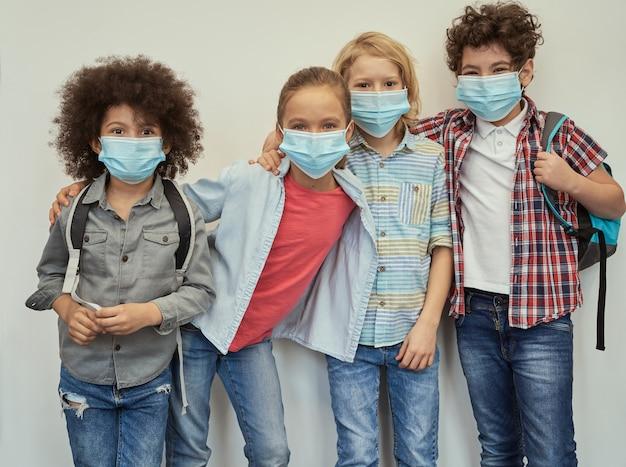 Entusiasta di studiare adorabili ragazzi delle scuole diverse che indossano maschere protettive che guardano looking