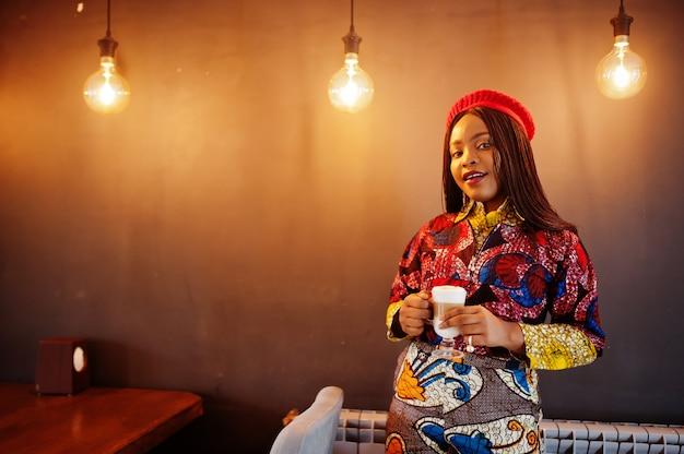 Entusiasta donna afro-americana in abito colorato alla moda con berretto rosso agghiacciante in accogliente caffetteria con una tazza di latte caldo nelle mani.