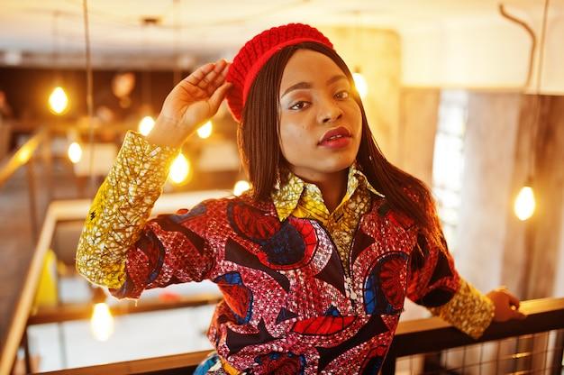 Entusiasta donna afro-americana in abito colorato alla moda con berretto rosso agghiacciante in accogliente caffetteria.