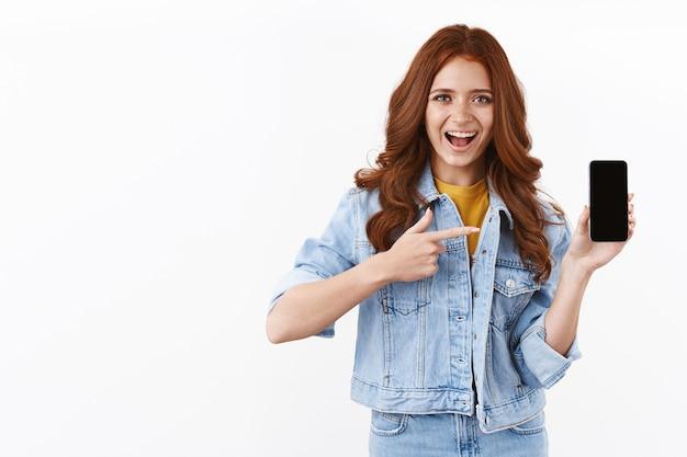 Entusiasta ragazza zenzero carina in giacca di jeans, tenere lo smartphone, puntare lo schermo del telefono cellulare e sorridere divertito, consigliare l'app, mostrare la pagina dei social media, in piedi muro bianco