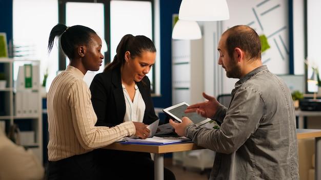 Entusiasti diversi uomini d'affari che leggono la relazione finanziaria annuale seduti al tavolo in un moderno ufficio aziendale di avvio che tiene tablet e sorridente. team di uomini d'affari multietnici che lavorano in azienda