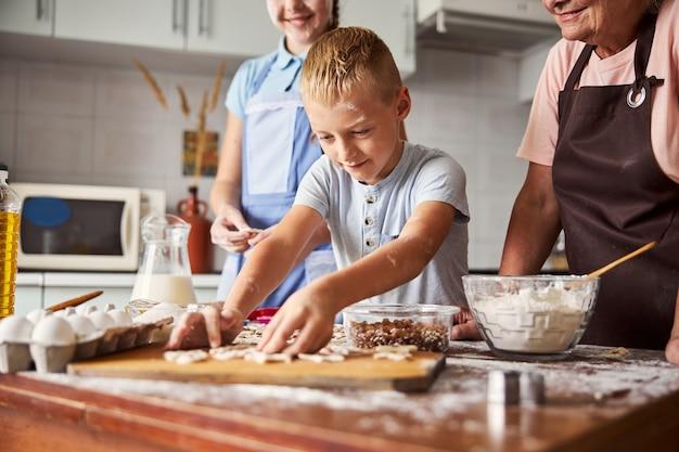 Piccolo chef entusiasta che prepara i biscotti con l'aiuto della sua famiglia