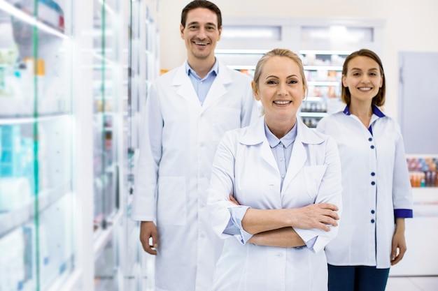 Tre farmacisti entusiasti che sorridono alla telecamera mentre si trovano in farmacia