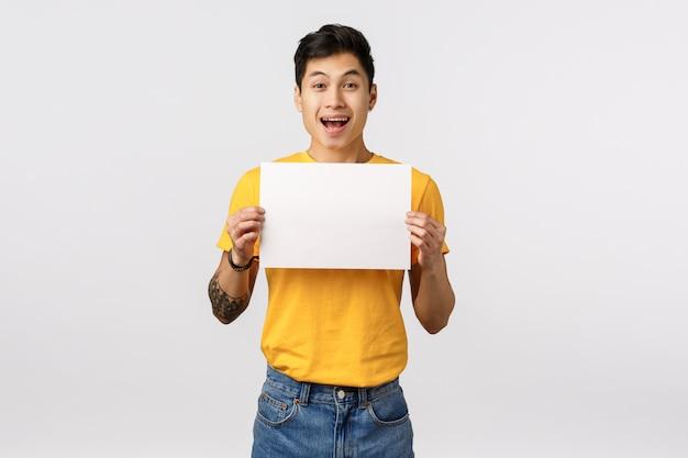 Entusiasta, elettrizzante bel ragazzo cinese con tatuaggi, con cartello, pezzo di carta bianca sul petto, promuovi l'offerta aziendale, sorridendo con gioia e felicità, in piedi muro bianco pubblicizza