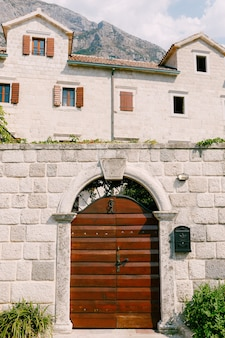 Ingresso al cortile da una porta metallica chiusa con elementi in ferro battuto nell'arco