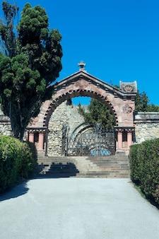 Ingresso a forma di arco in pietra e cancello in ferro con ringhiera con scale