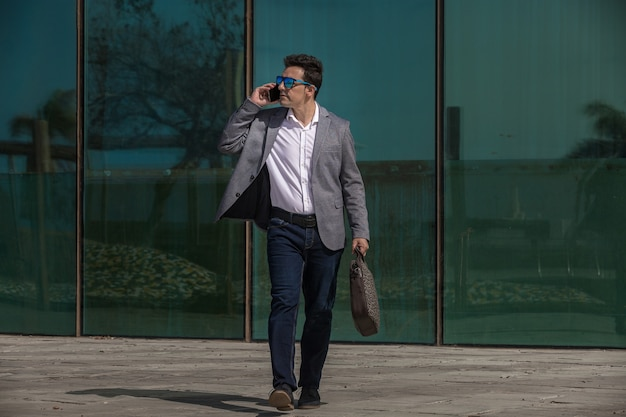 Imprenditore rispondendo alla telefonata durante la passeggiata sulla strada