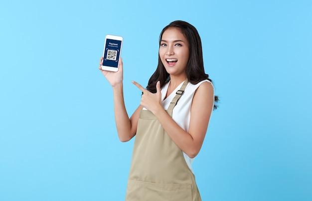 Donna asiatica imprenditrice che mostra il codice qr di scansione dello smartphone per il pagamento su sfondo blu.