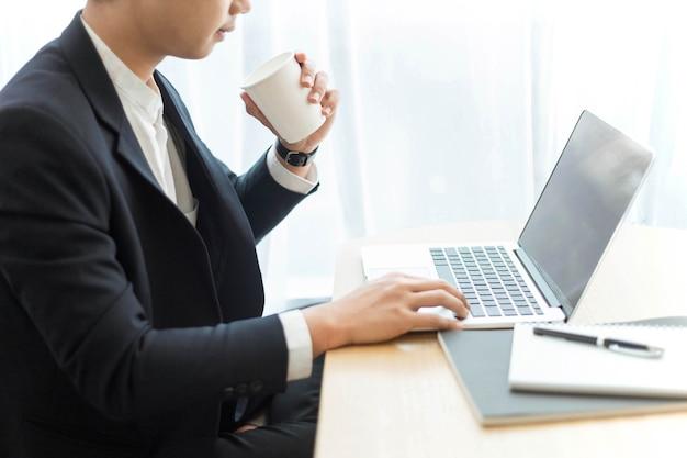 Concetto di imprenditore un uomo d'affari intelligente che lavora sul suo lavoro con i suoi dispositivi mentre si gode una tazza di bevanda.