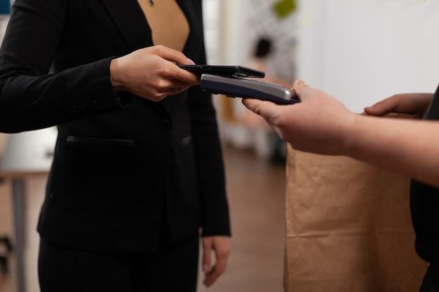Imprenditore che effettua pagamenti senza contatto utilizzando uno smartphone durante una transazione finanziaria non in contanti