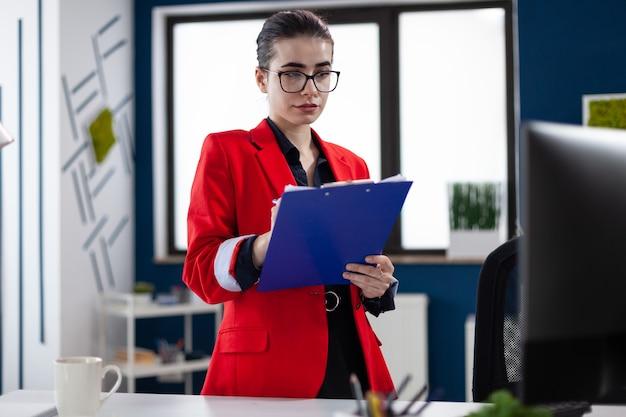 Imprenditore in piedi nel posto di lavoro dell'ufficio aziendale a prendere appunti