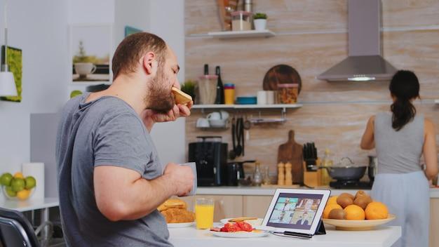 Imprenditore in videoconferenza mentre fa colazione in cucina. libero professionista che lavora a distanza, parla in videoconferenza videochiamata online web meeting internet da casa, dispositivo di comunicazione