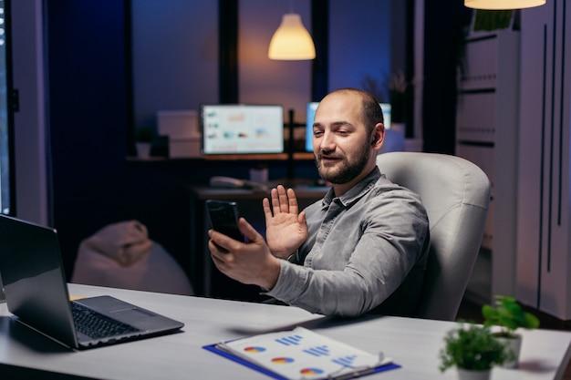 Imprenditore che saluta durante la chiamata online su smartphone con qualcuno. imprenditore nel corso di un'importante videoconferenza mentre fa gli straordinari in ufficio.