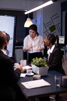 Strategia di gestione del brainstorming della donna imprenditrice che lavora sodo nella sala riunioni dell'ufficio a tarda notte. diversi team aziendali multietnici che guardano la presentazione della società finanziaria sul monitor.