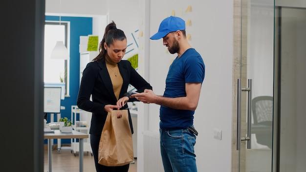 Imprenditrice che lavora in un ufficio aziendale che riceve cibo da asporto pranzo al sacco pagando l'ordine con smartwatch utilizzando il servizio contactless pos