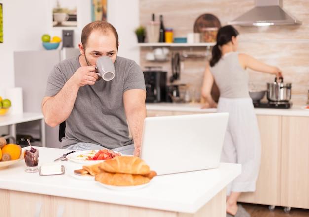 Imprenditore che lavora al computer portatile in cucina e beve caffè mentre la moglie prepara la colazione. il libero professionista lavora online via internet utilizzando la moderna tecnologia digitale