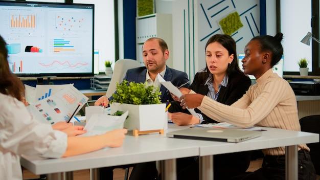Imprenditori e uomini d'affari conferenza discutendo nella moderna sala riunioni. dirigente che spiega la visione dell'azienda ai dipendenti seduti al tavolo di brainstorming in un'ampia sala con schermo tv