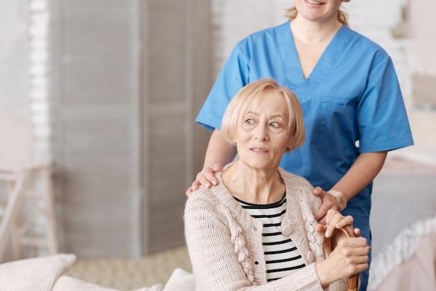 Affidare la mia salute a un esperto. bella signora anziana sognante seduta nel suo salotto e con un visitatore dall'ospedale locale che si prende cura della sua salute