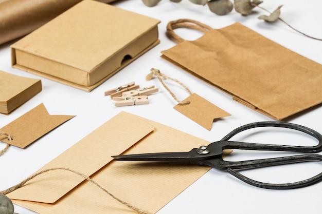 Avvolgere, sacchetto, etichetta, carta e altri articoli per ufficio su una scrivania bianca