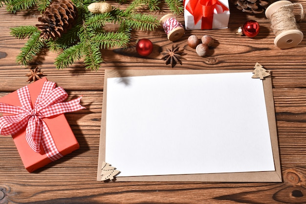 Una busta e un foglio bianco su un tole di legno con decorazioni natalizie. buon anno. copia spazio. disposizione piana, vista dall'alto.
