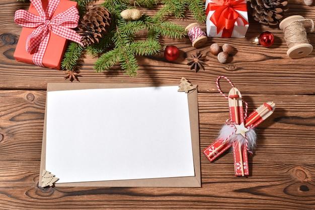 Una busta e un foglio bianco su un tole di legno con decorazioni natalizie.