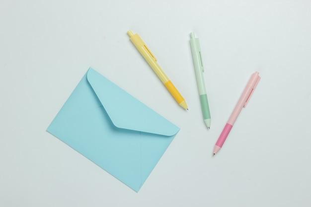 Busta e penne colorate su sfondo bianco. vista dall'alto