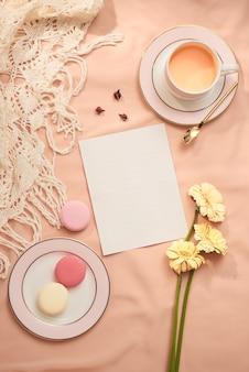 Busta, fiori e macarons con una tazza di tè su sfondo chiaro