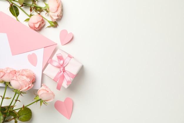 Busta, rose, cuori e confezione regalo su sfondo bianco