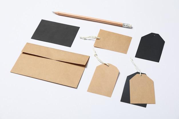 Busta, etichette e matita su fondo bianco