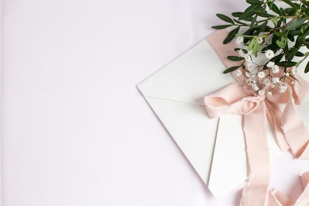 Busta su fondo bianco-rosa con nastro di seta color pesca, ramo verde e fiori. invito a nozze. biglietto per la festa della mamma. posto per il testo. copia spazio.